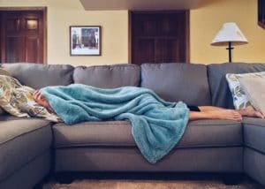 Sick person lying under a blanket on their couch