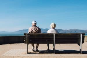 Old couple sitting on a bench looking at the scenery
