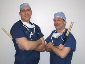 Two doctor-musicians posing with their drumsticks