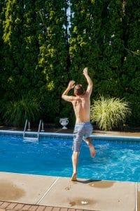 child jumping into a backyard pool