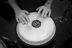 person playing a bongo drum